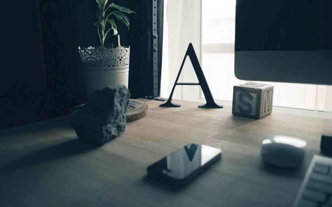 Letter A with plant and items on a desk